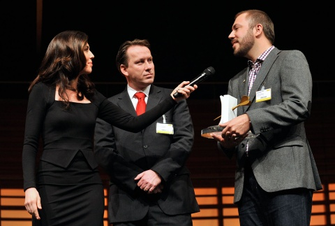 Preisgekrönt: Creative Director Tommy Schilling (r.) und Coop Marketingleiter Thomas Schwetje (m.) nehmen von Susanne Wille die Swiss Marketing Trophy 2012 entgegen.